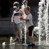 Two boys catch water jet in the fountain