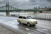 Trabant car moving along river, Szabadsag bridge